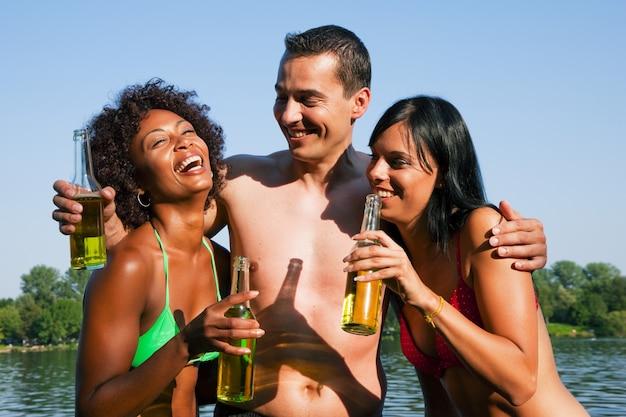 Grupo de amigos, bebendo cerveja em trajes de banho