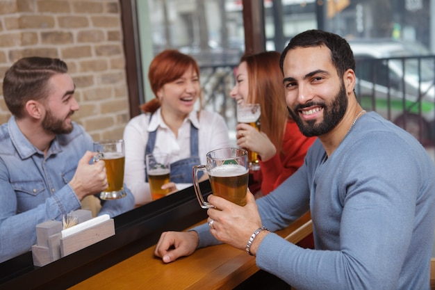 Grupo de amigos bebendo cerveja no bar juntos