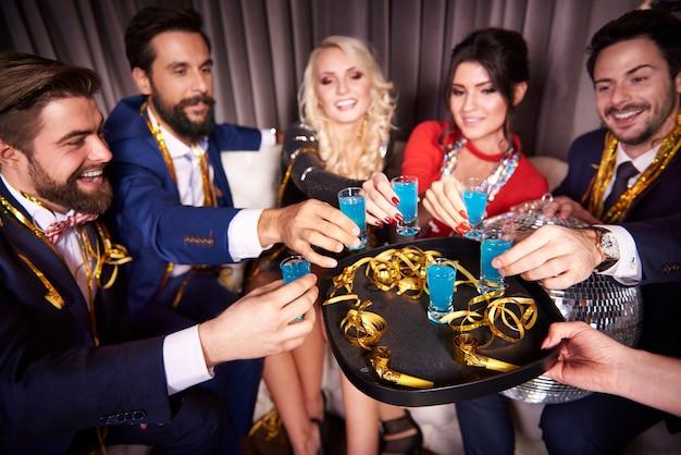 Grupo de amigos bebendo curaçao azul em boate