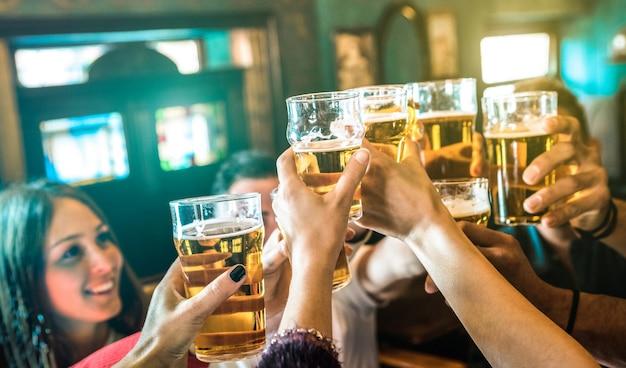 Grupo de amigos bebendo e brindando cerveja em bar restaurante cervejaria