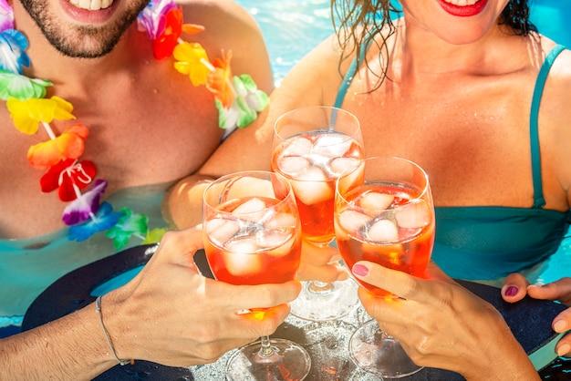 Grupo de amigos bebendo juntos na piscina