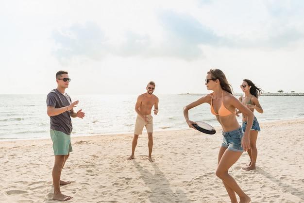 Grupo de amigos brincando na praia em férias de verão