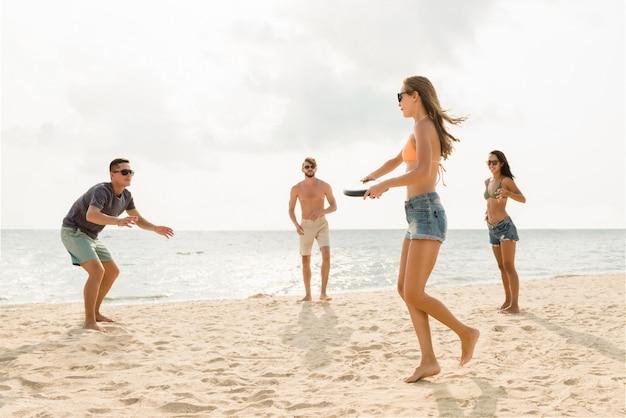Grupo de amigos brincando na praia nas férias de verão