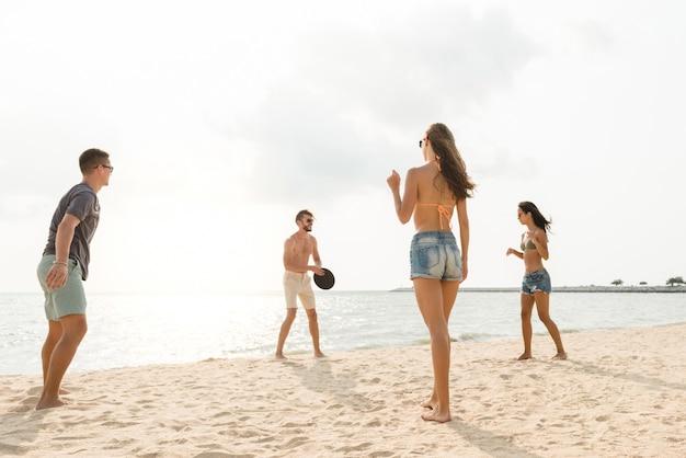 Grupo de amigos brincando na praia no verão