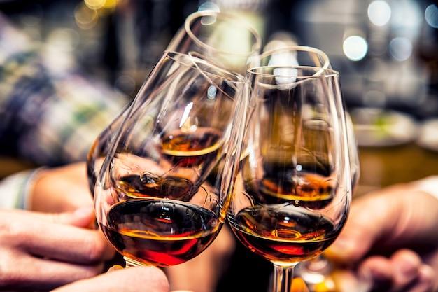 Grupo de amigos brindando à saúde de rum ou conhaque de conhaque.