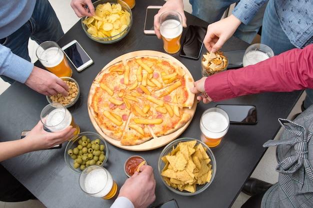 Grupo de amigos brindando com cerveja e comendo pizza