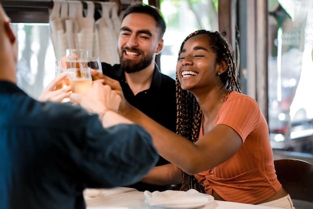 Grupo de amigos brindando com copos de cerveja em um restaurante.