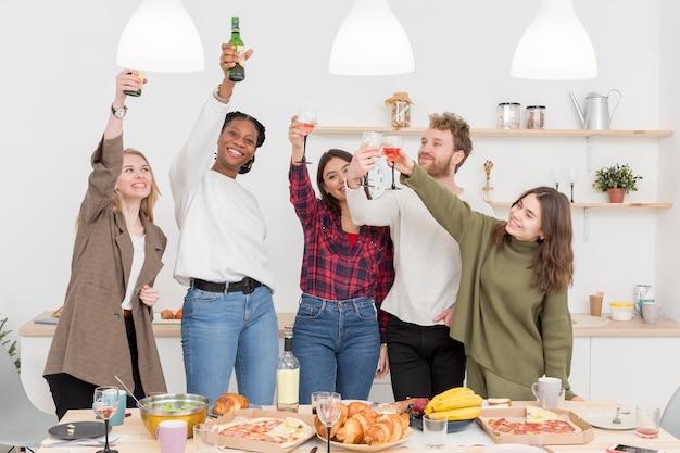 Grupo de amigos brindando enquanto come