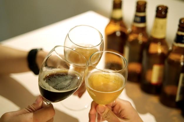 Grupo de amigos brindando o copo de cerveja no quarto.