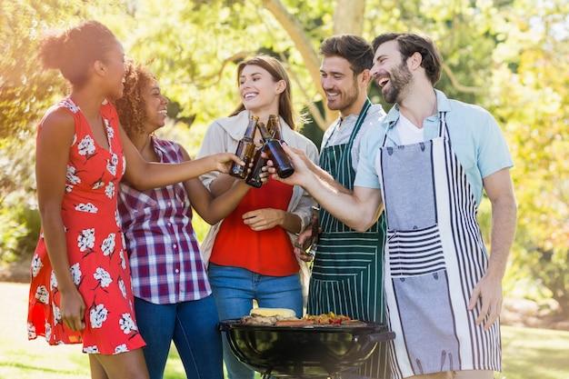 Grupo de amigos brindando uma garrafa de cerveja enquanto prepara churrasqueira
