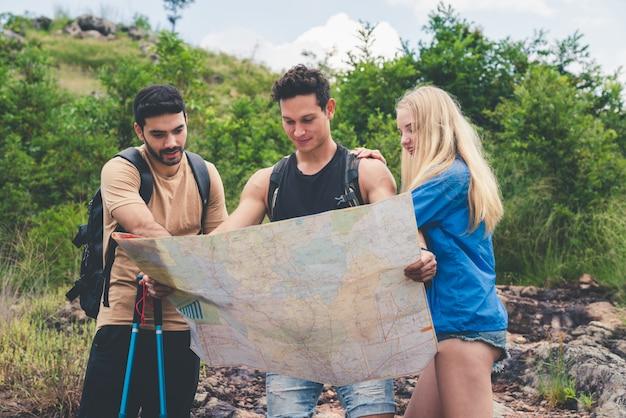 Grupo de amigos, caminhadas com mochilas, olhando para o mapa, encontrar instruções para viajar na montanha