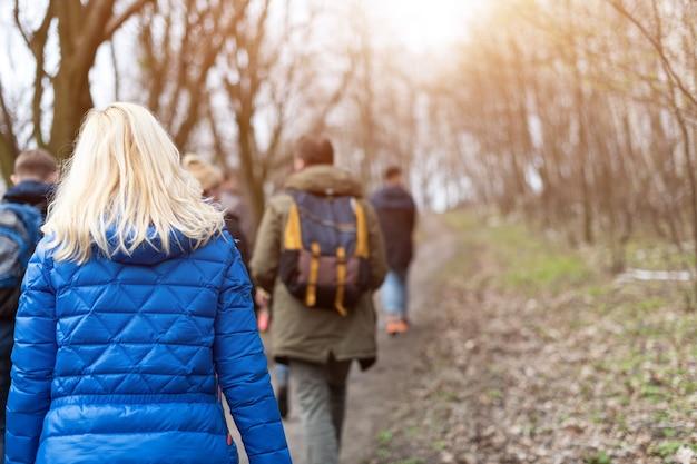 Grupo de amigos caminhando com mochilas na floresta da primavera, nos fundos