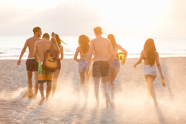 Grupo de amigos, caminhando na praia ao pôr do sol.