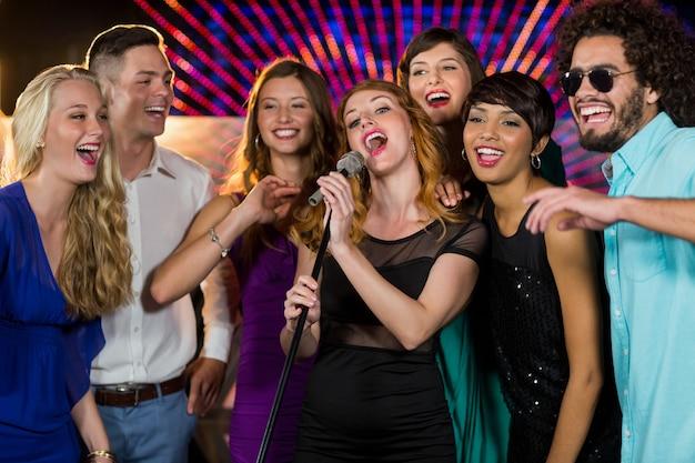 Grupo de amigos cantando música juntos no bar