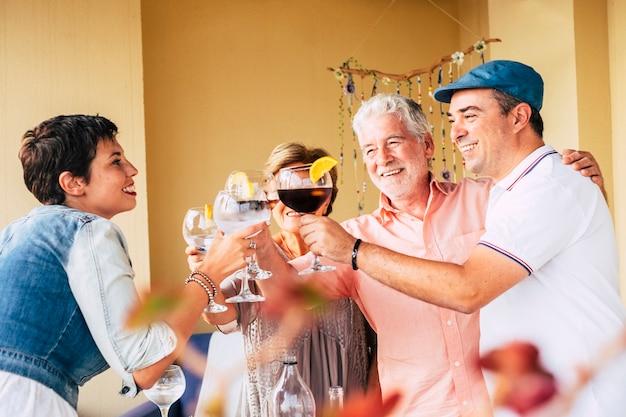 Grupo de amigos caucasianos de diferentes idades, homens e mulheres brindando se divertindo durante um almoço comemorativo em amizade