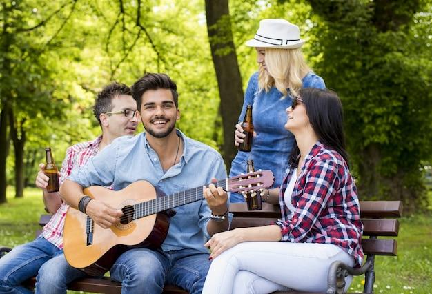 Grupo de amigos caucasianos tocando violão, bebendo cerveja e se divertindo em um banco de parque