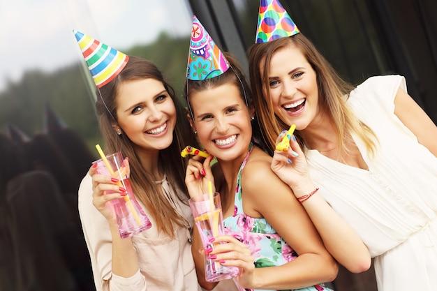 Grupo de amigos com assobios e bebidas comemorando aniversário