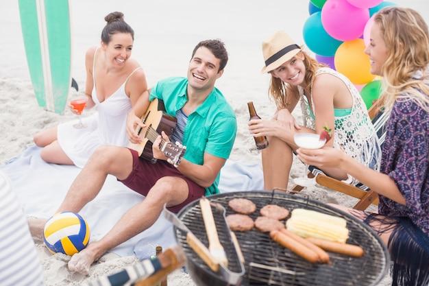 Grupo de amigos com bebidas e violão, sentado ao lado de um churrasco
