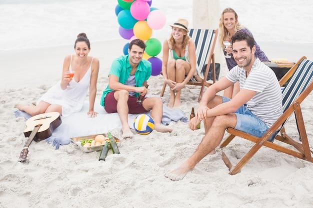 Grupo de amigos com bebidas se divertindo juntos na praia