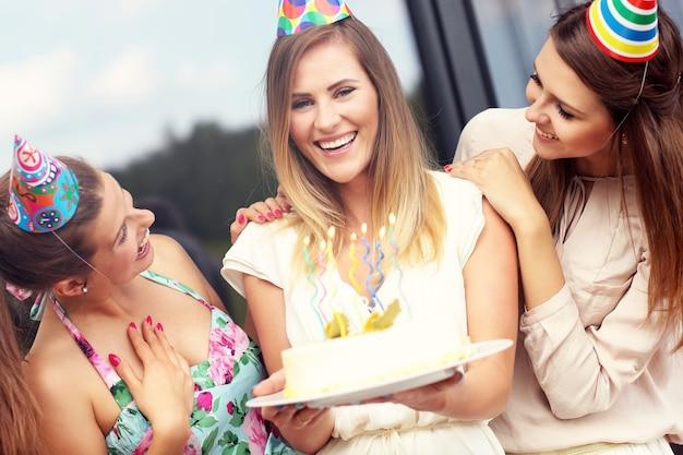 Grupo de amigos com bolo comemorando aniversário