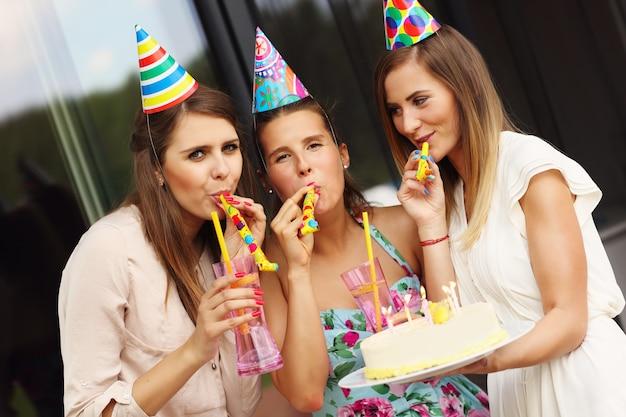 Grupo de amigos com bolo e bebidas comemorando aniversário