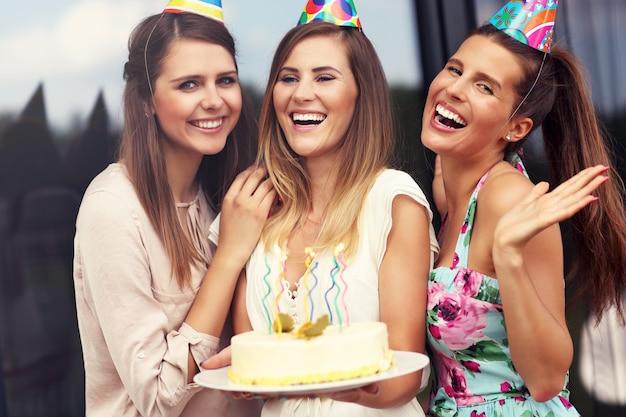 Grupo de amigos com bolo e presentes comemorando aniversário
