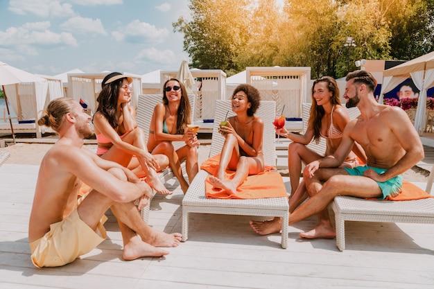 Grupo de amigos com maiô toma um coquetel em casa de praia