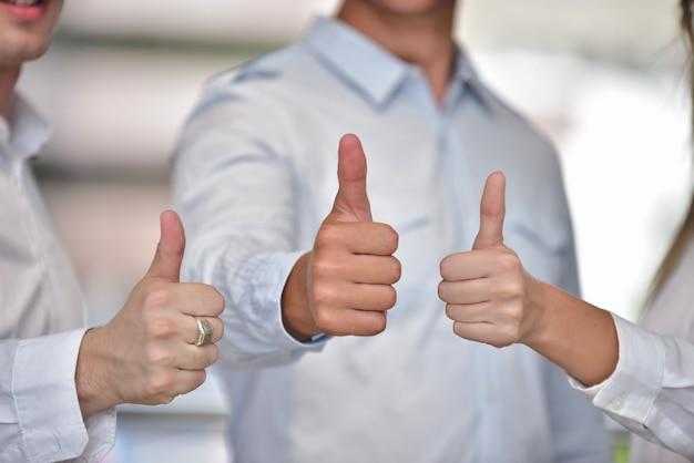 Grupo de amigos com polegares para cima. retrato do homem novo feliz e da mulher que dão os polegares acima.