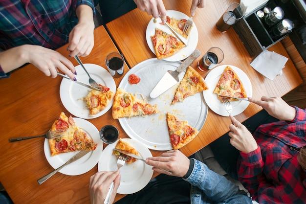Grupo de amigos come pizza italiana