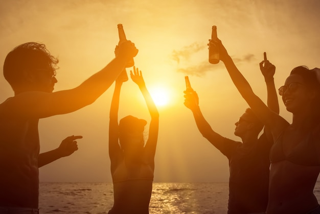 Grupo de amigos comemorando e bebendo na praia no crepúsculo do sol