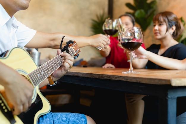 Grupo de amigos comemorando e tocando violão enquanto bebe vinho tinto.