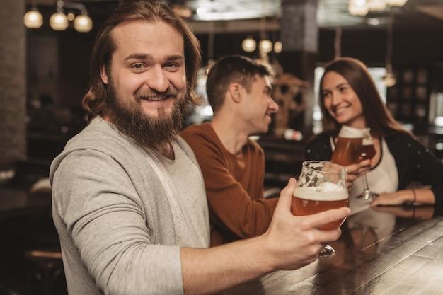 Grupo de amigos comemorando no pub, bebendo cerveja juntos