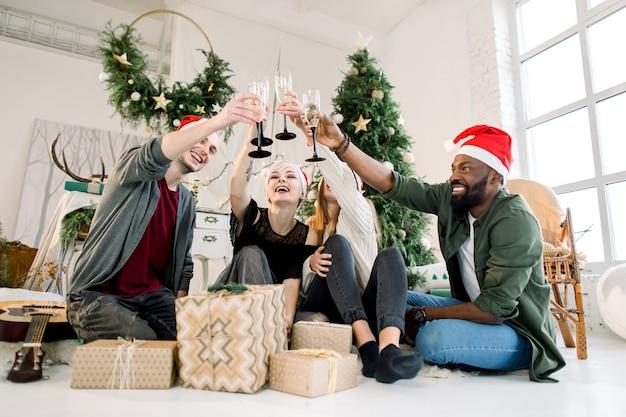 Grupo de amigos comemorando o natal em casa e brindando com champanhe