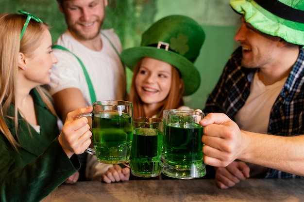 Grupo de amigos comemorando st. dia de patrick juntos no bar com bebidas