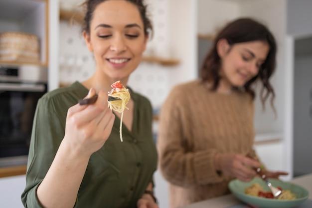 Grupo de amigos comendo macarrão juntos na cozinha