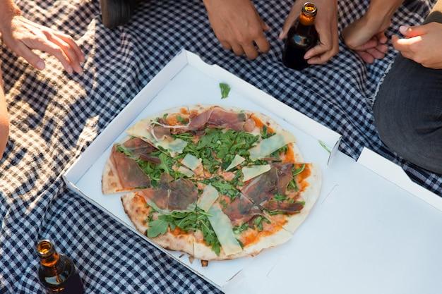 Grupo de amigos comendo pizza ao ar livre