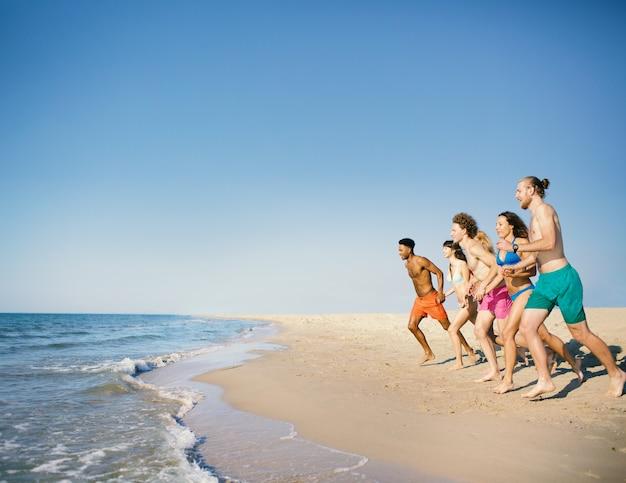 Grupo de amigos corre no mar azul. conceito de verão