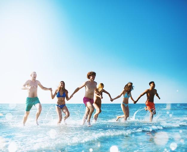 Grupo de amigos corre no mar conceito de verão