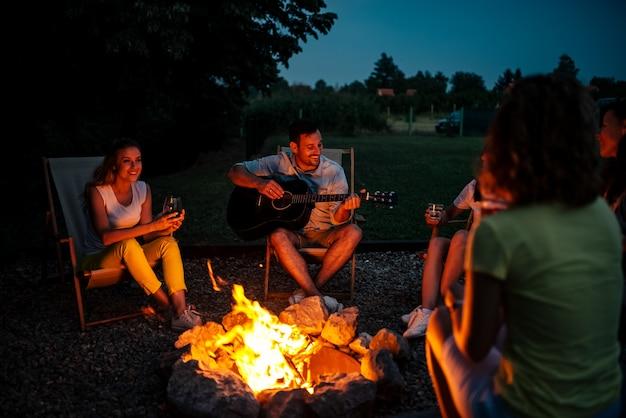 Grupo de amigos curtindo música ao redor da fogueira à noite.