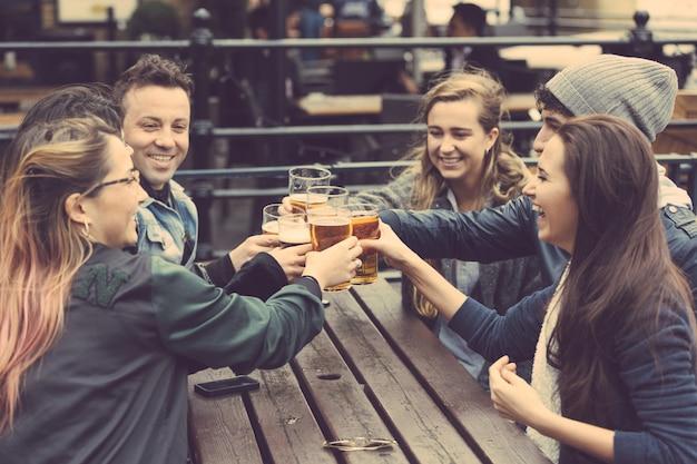 Grupo de amigos, curtindo uma cerveja no pub em londres