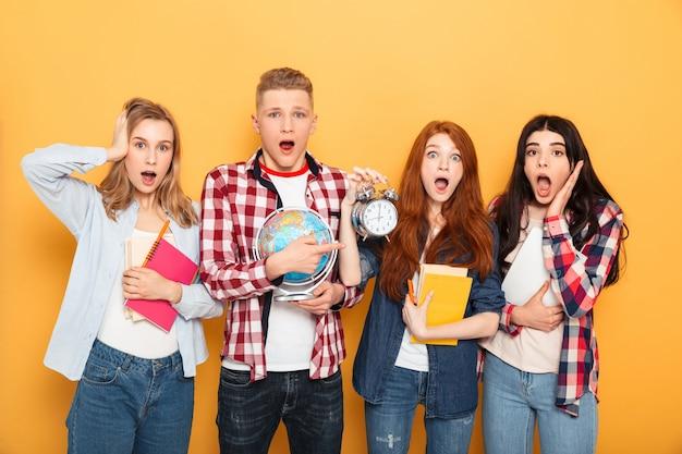 Grupo de amigos da escola chocados mostrando despertador