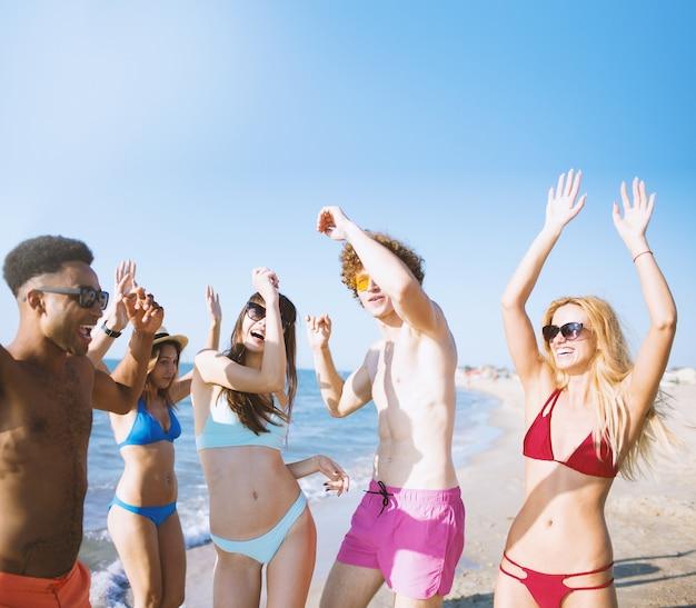 Grupo de amigos dançando música disco na praia