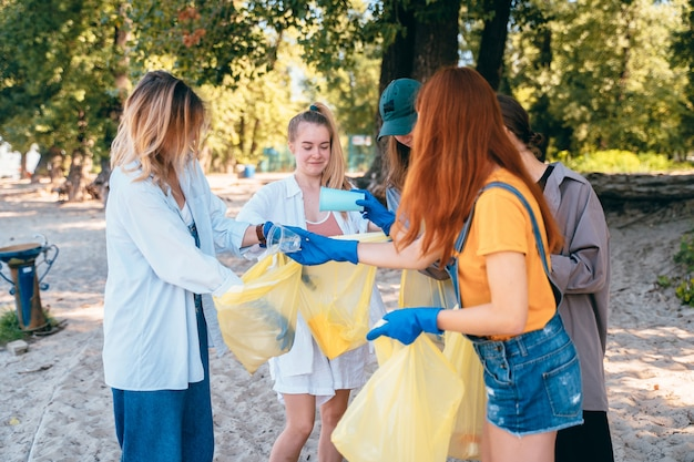 Grupo de amigos de ativistas que coletam resíduos plásticos na praia. conservação ambiental.