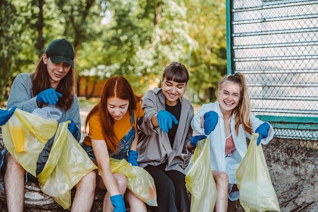 Grupo de amigos de ativistas que coletam resíduos plásticos no parque. conservação ambiental.