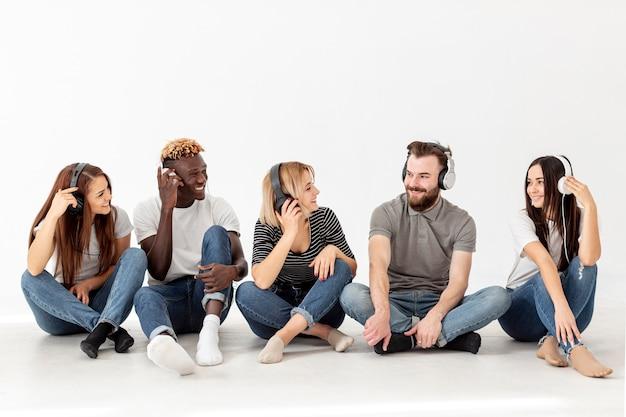 Grupo de amigos de cópia-espaço sentado no chão