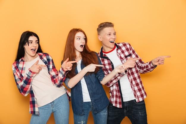 Grupo de amigos de escola empolgados apontando o dedo para longe