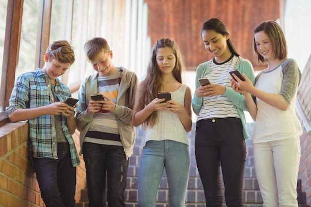Grupo de amigos de escola sorridentes usando telefone celular no corredor