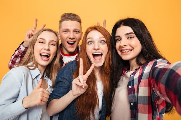 Grupo de amigos de escola sorrindo tirando uma selfie
