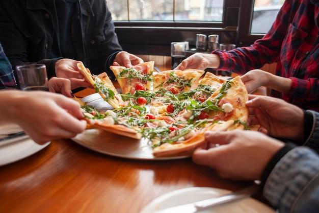 Grupo de amigos de estudantes comem pizza italiana