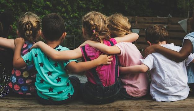 Grupo de amigos de jardim de infância amigos abraçados sentados juntos